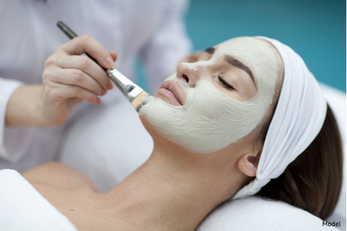 A woman receiving a facial to prevent skin damage. Her skin care regimen includes professional treatment and a proper diet.